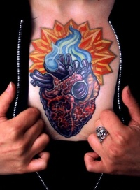 Colorful heart tattoo on chest by Mike Cole