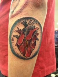 Coloured heart forearm tattoo by Iris Lys