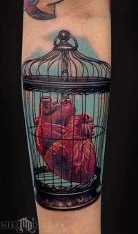 Coloured heart in a bird cage tattoo