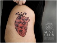Heart of red roses tattoo on thigh